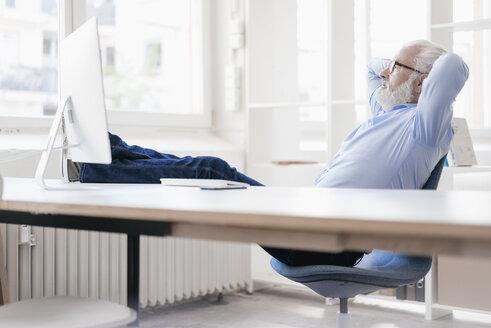 Mature man with beard relaxing at desk - JOSF01707