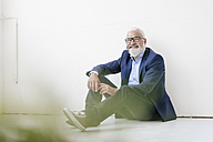 Smiling mature man sitting on the floor - JOSF01710