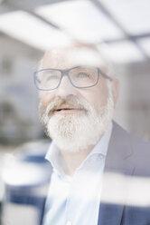 Portrait of mature man behind windowpane - JOSF01716