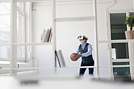 Mature man wearing VR glasses playing basketball in office - JOSF01722