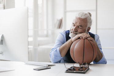 Relaxed mature man on at desk with basketball - JOSF01725
