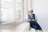 Mature man with tablet and headphones at the window - JOSF01728