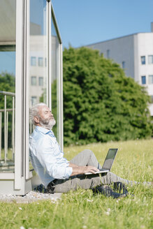 Mature man with laptop relaxing on meadow - JOSF01734