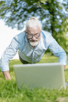 Mature man with laptop exercising in park - JOSF01740