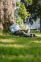 Mature man with laptop relaxing in park - JOSF01743