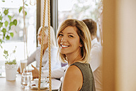 Portrait of smiling young woman in a cafe - ZEDF00842