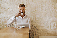 Man with tablet drinking espresso in a cafe - ZEDF00848