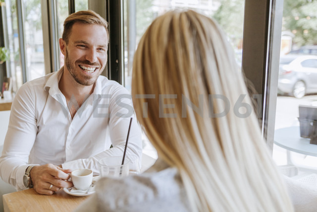 Happy man looking at woman in a cafe - ZEDF00851