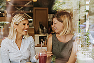 Two happy young women in a cafe - ZEDF00860