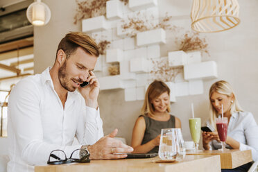 Man on cell phone in a cafe with two women in background - ZEDF00863