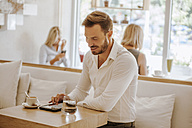 Man using tablet in a cafe with two women in background - ZEDF00866