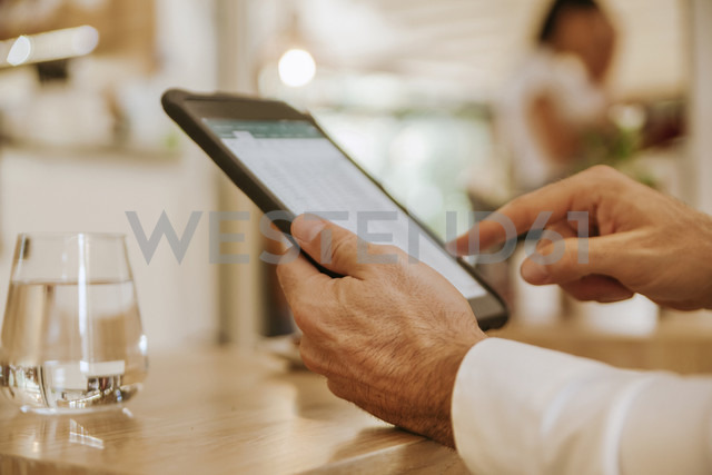 Close-up of man using tablet in a cafe - ZEDF00869