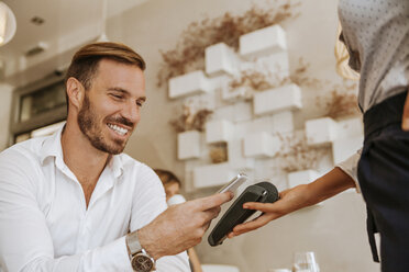 Smiling man paying with smart phone in cafe - ZEDF00878