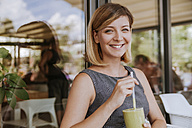 Portrait of smiling young woman with smoothie in a cafe - ZEDF00884