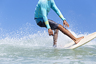 Indonesia, Bali, legs of surfer on a wave - KNTF00897