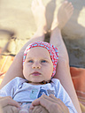 Portrait of baby girl lying on mother's legs on the beach - LAF01884