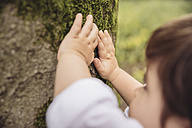 Toddler's hands feeling tree moss in park - MFF03970