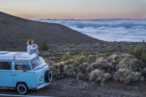 Spain, Tenerife, woman sitting on car roof of van at twilight looking at view - SIPF01757
