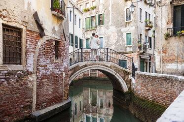 Italy, Venice, bridal couple standing  on little bridge - DIGF02851