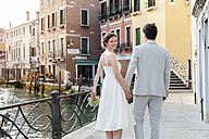 Italy, Venice, happy bridal couple walking hand in hand - DIGF02860