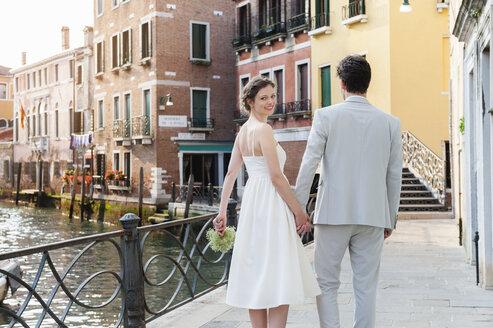 Italy, Venice, happy bridal couple walking hand in hand - DIGF02860