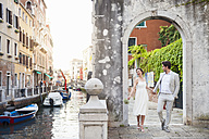 Italy, Venice, bridal couple walking hand in hand through archway - DIGF02863