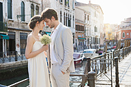 Italy, Venice, bridal couple standing head to head in front of canal - DIGF02866