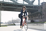 Smiling businessman riding bicycle at riverside bridge - SBOF00675