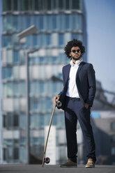 Businessman with longboard standing in front of skyscraper - SBOF00684