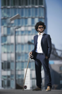 Businessman with longboard standing in front of skyscraper - SBOF00684