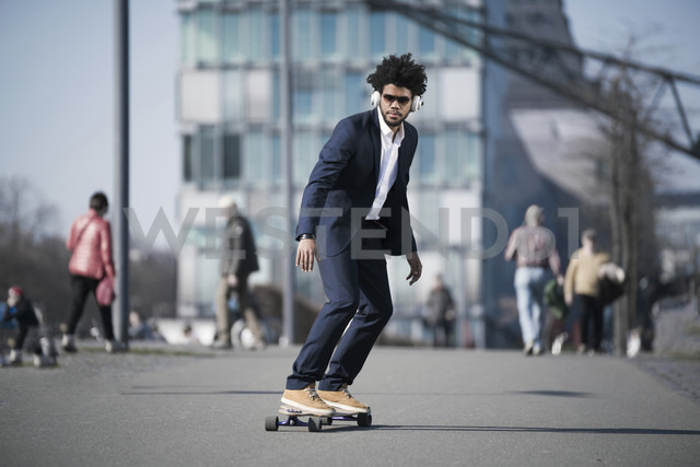 Businessman riding longboard in front of skyscraper - SBOF00687