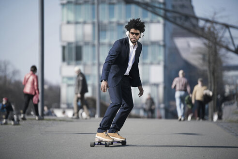 Businessman riding longboard in front of skyscraper - SBOF00687