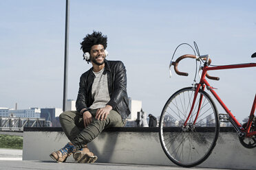 Smiling man listening to music on headphones next to his bicycle - SBOF00690