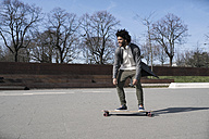 Smiling young man riding longboard in skatepark - SBOF00693