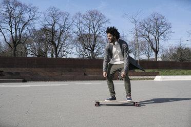 Smiling young man riding longboard in skatepark - SBOF00693