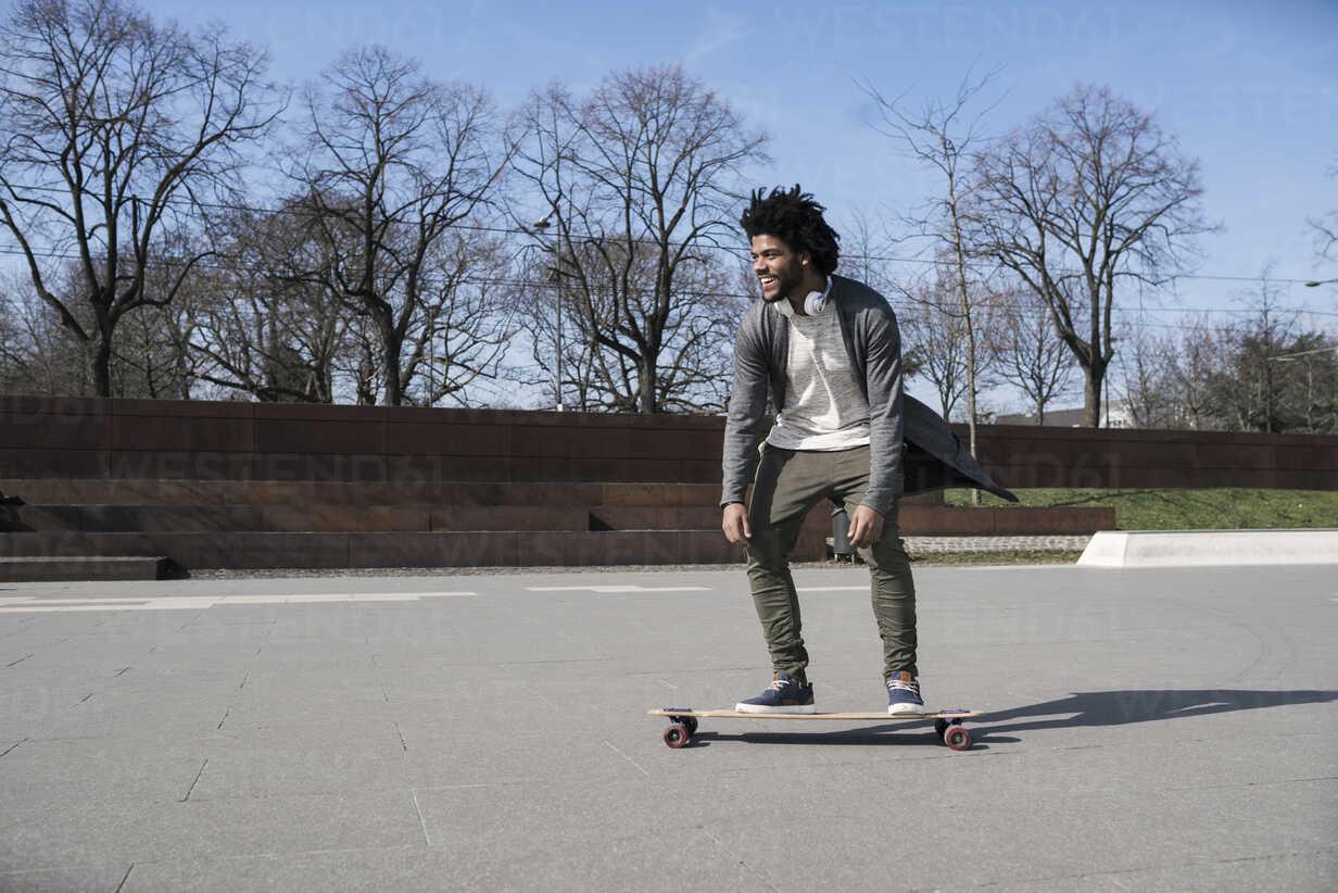 Smiling young man riding longboard in skatepark - SBOF00693 - Steve Brookland/Westend61