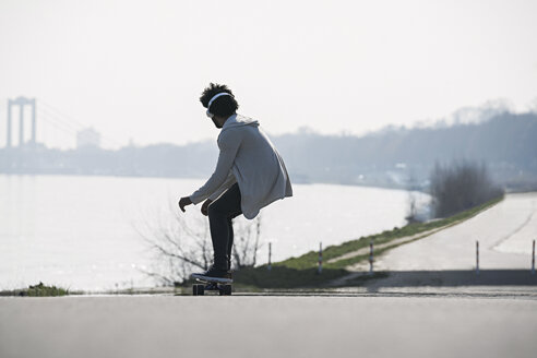 Young man riding longboard at the riverside - SBOF00696