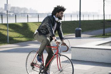 Smiling man riding bicycle at the riverside - SBOF00699