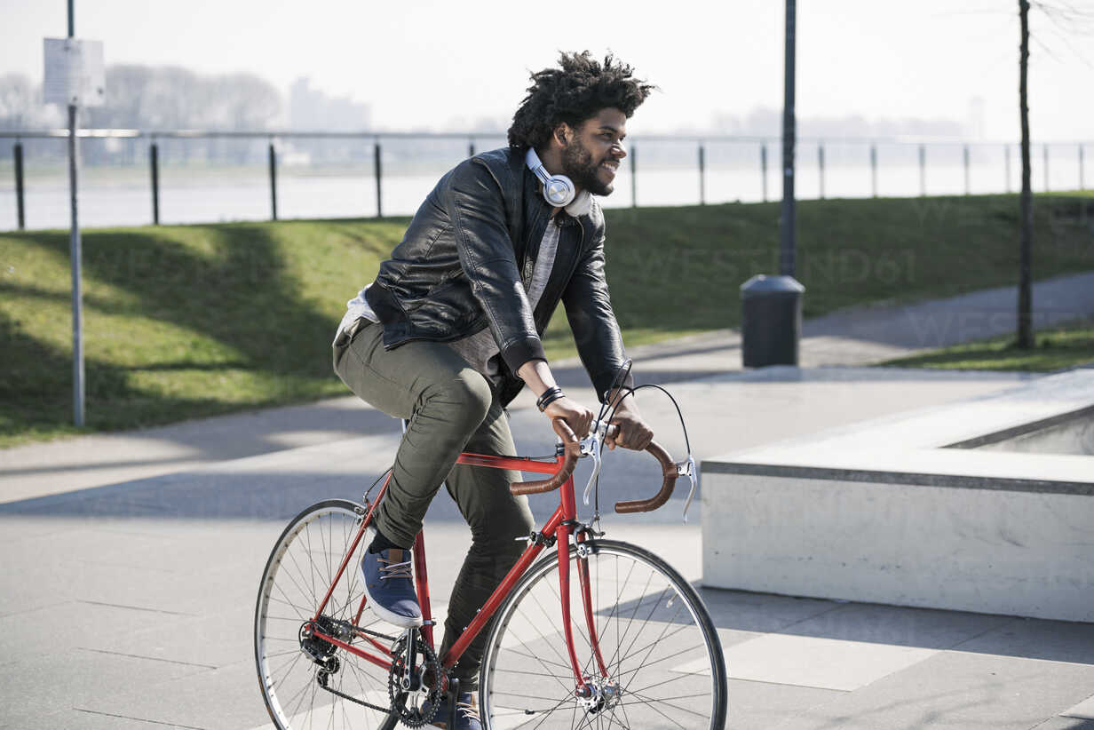 Smiling man riding bicycle at the riverside - SBOF00699 - Steve Brookland/Westend61