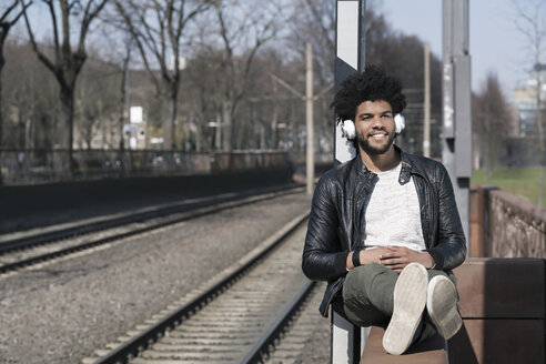 Smiling man sitting on wall listening to music next to  train rails - SBOF00702