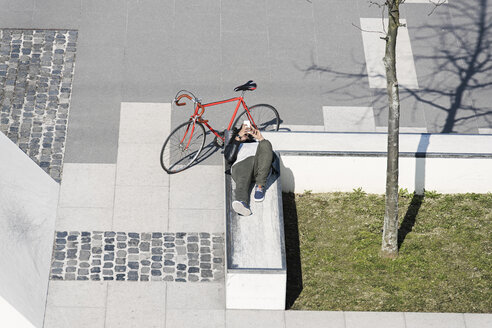 Man relaxing in city skatepark with smartphone next to his bicycle - SBOF00705
