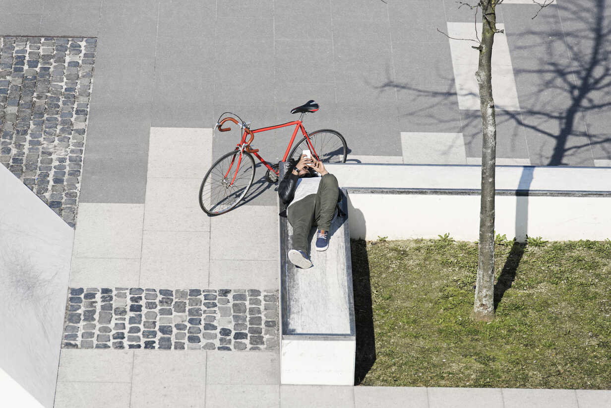 Man relaxing in city skatepark with smartphone next to his bicycle - SBOF00705 - Steve Brookland/Westend61