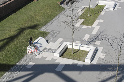 Man sitting in city skatepark with smartphone next to his bicycle - SBOF00708