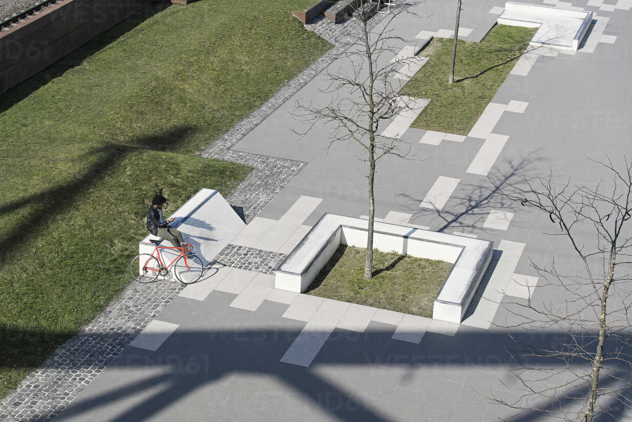 Man sitting in city skatepark with smartphone next to his bicycle - SBOF00708 - Steve Brookland/Westend61