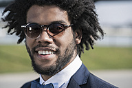 Portrait of smiling young man with sunglasses - SBOF00717