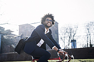 Smiling businessman with sunglasses riding bicycle in the city - SBOF00720