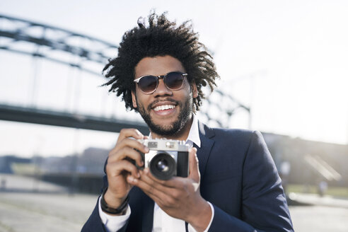 Smiling man in suit at the riverside holding a vintage camera - SBOF00723