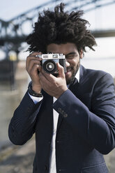 Man in suit at the riverside taking a picture with a vintage camera - SBOF00726