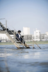 Businessman sitting on stairs at the river using laptop - SBOF00729