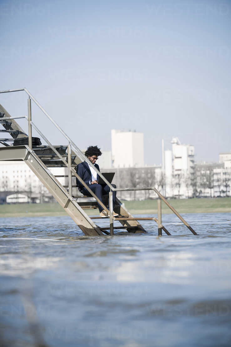 Businessman sitting on stairs at the river using laptop - SBOF00729 - Steve Brookland/Westend61
